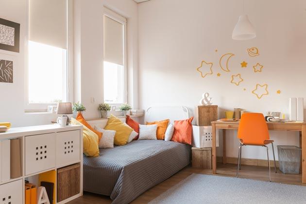 С акцентами в оранжевом цвете на декоре и подушках