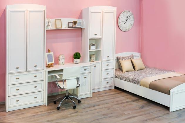 Белая мебель в комнате для девочки на фоне стен в розовых тонах