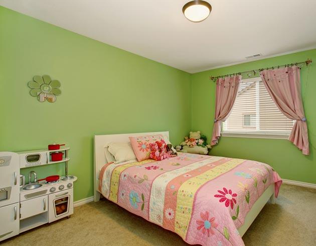 Светло-зеленые стены в интерьере разбавлены цветочными шторами и покрывалом