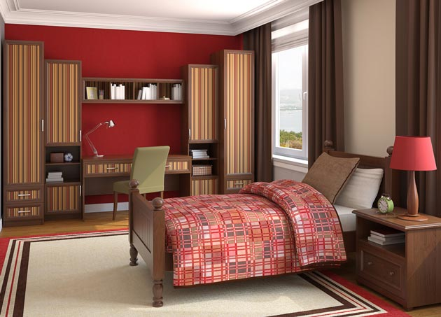 Коричневая мебель для подростка на фоне красной стены и точечного использования цвета