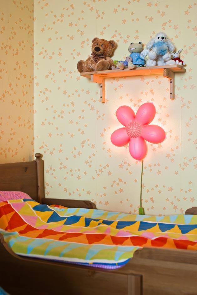 С настенным светильником в форме цветка у кровати