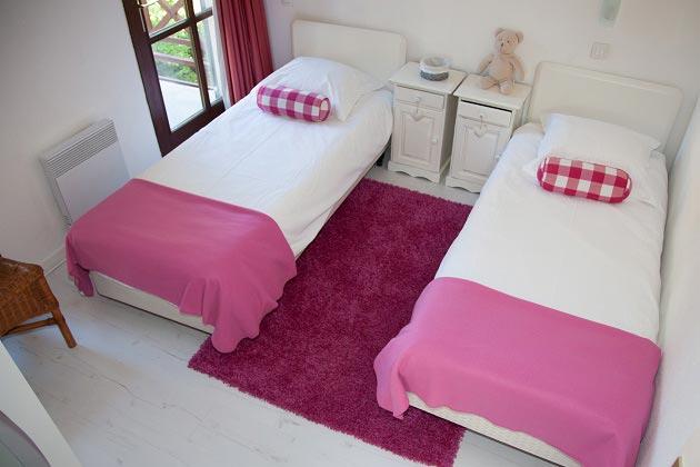 Две кровати с одинаковым текстилем, разделенные тумбочками
