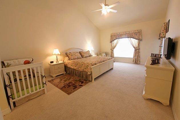Просторная спальня родителей с детской кроваткой