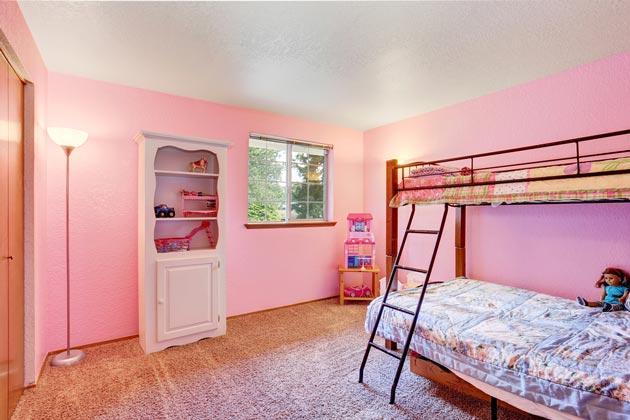 Интерьер в розовом цвете с двухэтажной кроватью и белым стеллажом