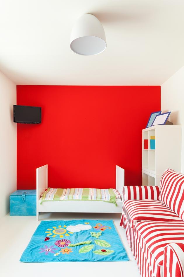 Алый на одной из стен в гармонии с диваном в красно-белую полоску