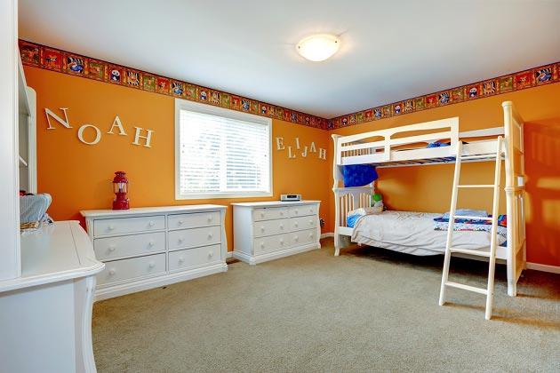 Интерьер детской в оранжевом цвете для двоих детей с белой мебелью