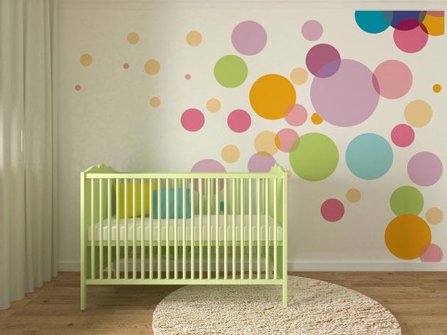 Салатовая кроватка у стены с рисунком из разноцветных кругов