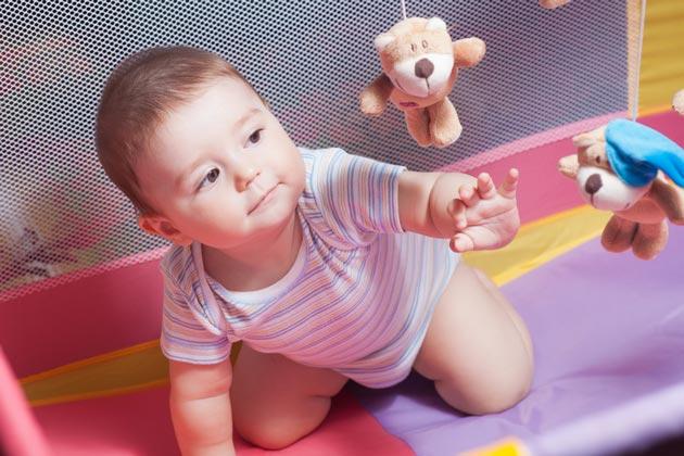 Маленький ребенок играет в детском манеже