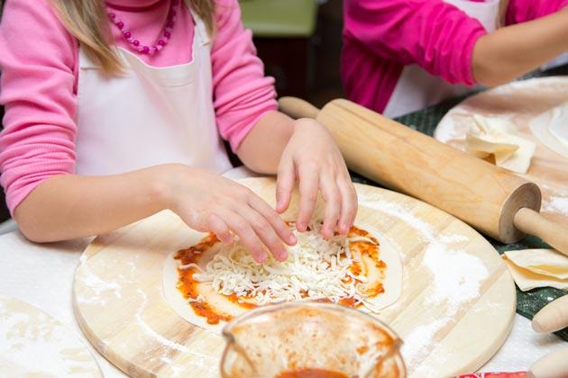 Маленькая девочка готовит пиццу