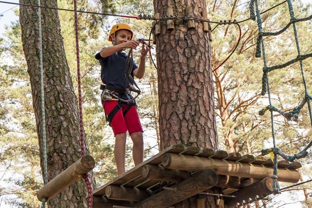 Мальчик подросток в веревочном парке развлечений