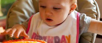Ребенок 1 года за праздничным столом с тортом