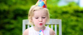 Девочка задувает торт со свечкой в форме цифры 3