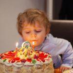 Малыш задувает торт с двумя свечками