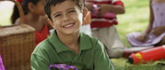 Мальчик 8 лет в праздничном колпачке с подарками